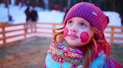 Little girl with painted face in hat looks up outdoor Stock Footage
