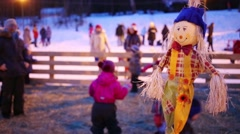 Bright straw puppet and playing children out of focus at winter Stock Footage