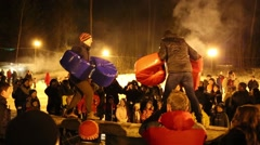 Two men fight on log at night during Shrovetide Stock Footage