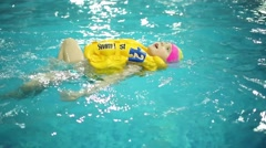 Happy little cute girl in yellow inflatable vest swim in pure pool Stock Footage
