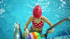 Little girl in swimming cap swim with styrofoam in pure pool Stock Footage