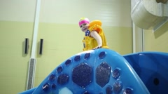 Happy little girl in yellow inflatable vest down on slide Snake in pool Stock Footage