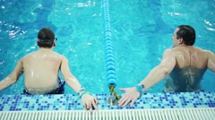 Young man and boy teen swim and compete in  blue pool Stock Footage