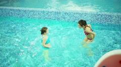 Two happy girls in swimsuits dance in indoor pool with pure water Stock Footage
