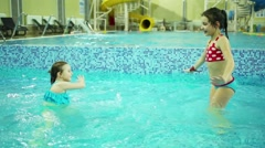 Two girls in swimsuits dance in indoor pool with pure water Stock Footage
