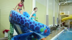 Two girls in swimsuits down on slide Snake in indoor pool Stock Footage