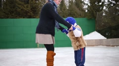Teenager girl teaches younger brother of skate at rink Stock Footage