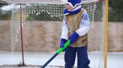 Little cute boy with hockey stick stands near gate at rink Stock Footage