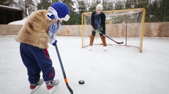 Girl teaches younger brother of play hockey at rink in winter day Stock Footage