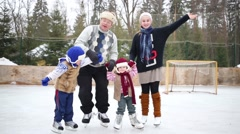 Father with three happy children stands on ice rink in winter day Stock Footage