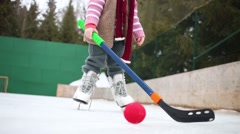 Happy little girl stands on skates with hockey stick at rink Stock Footage