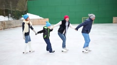 Mother, father, daughter and son skate on ice rink Stock Footage
