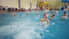 Adults and children play in indoor pool in Holiday House Stock Footage