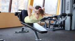 Young woman does exercises on simulator in fitness club Stock Footage