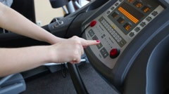 Female hands configure treadmill. Text on panel: Stop, start Stock Footage