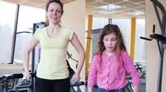 Young woman with daughter do exercises with dumbbells in fitness club Stock Footage
