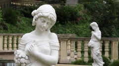 White statues sculptures of young ladies in a garden Stock Footage