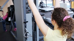 Woman does exercise for arm muscles on simulator in fitness club Stock Footage