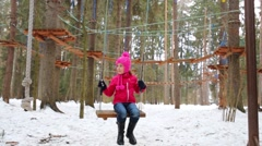 Girl swings in monkey park with rope path in winter forest Stock Footage