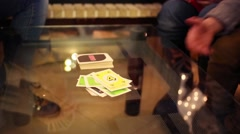 Hands and knees of four people playing table game with cards in room - stock footage