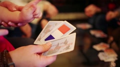 Hands of five people playing table game with cards with flags Stock Footage