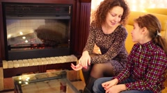 Happy mother and daughter sit on couch near fireplace in room Stock Footage