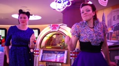Two women dance near Jukebox in Beverly Hills Diner Stock Footage