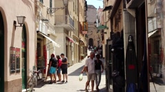 People browse restaurant menu and shop window in narrow, medieval street - stock footage