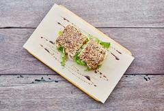 Fresh sandwich with crisp lettuce on a rustic wooden table - stock photo