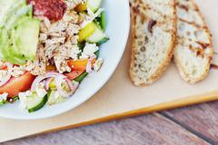 Colourful salad with fresh ingredients alongside sliced bread Stock Photos