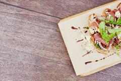 Bruschetta with fresh parma ham, rocket and pesto - stock photo