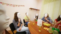 Ten young people hide faces by masks and sit at table Stock Footage