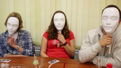 Three young people hide faces by masks and sit at table Stock Footage