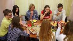 Eleven young people sit at table and eat pizza during birthday Stock Footage