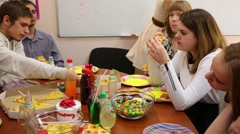 Nine teenager sit at table and eat during birthday Stock Footage