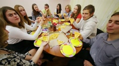 Eleven teenagers sit at table, talk and eat pizza at birthday Stock Footage