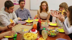 Seven teenagers sit at table, talk and eat pizza at birthday Stock Footage