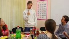 Five teenagers sit at table, eat and play pantomime game at birthday Stock Footage