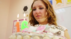 Girl teenager blows out candles 16 on cake at birthday Stock Footage