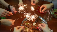 Eight teenagers sit at table and lit sparklers at birthday Stock Footage