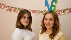 Girl with 16 on head and her friend laugh. Text on wall: happy birthday Stock Footage