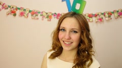 Girl with 16 on head smiles and waves hand. Text on wall: happy birthday Stock Footage