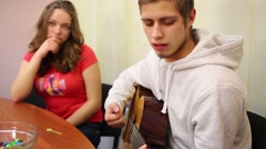 Boy teenager sings and plays guitar and girl listens him in room Stock Footage