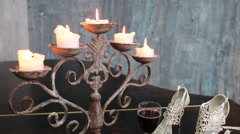 Candles on candlestick, shoes, beads and glass on grand piano Stock Footage