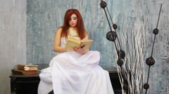 Pretty woman in dress sits on black grand piano and reads old book Stock Footage
