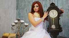 Pretty woman in white dress holds clock near candlestick Stock Footage