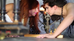 Two women look at each other near chess and candles under grand piano Stock Footage