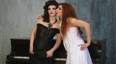 Two women in dresses pose near old black grand piano in studio - stock footage