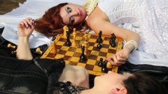 Two pretty women in black and white dresses lie and play chess Stock Footage