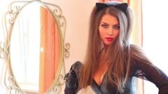 Pretty woman Cat in leather costume poses near mirror in bedroom Stock Footage